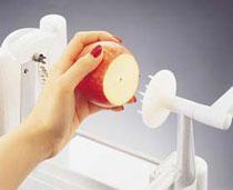 Pričvrstite voće/povrće na metalni kružić i zatim nežno pričvrstite drugu stranu za zubiće ručke na suprotnom kraju aparata.